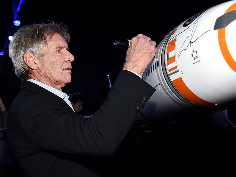 Harrison Ford who plays Star Wars character Han Solo autographs a 1/20 scale BB-8 ANA JET produced by PacMin // Photo courtesy of All Nippon Airways