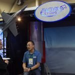 William To, Director of Engineering and Technology, speaks with a guest at EXHIBITORLIVE.