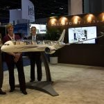 Greenpoint Technologies - 2 men and 1 woman standing next to display-size airplane model