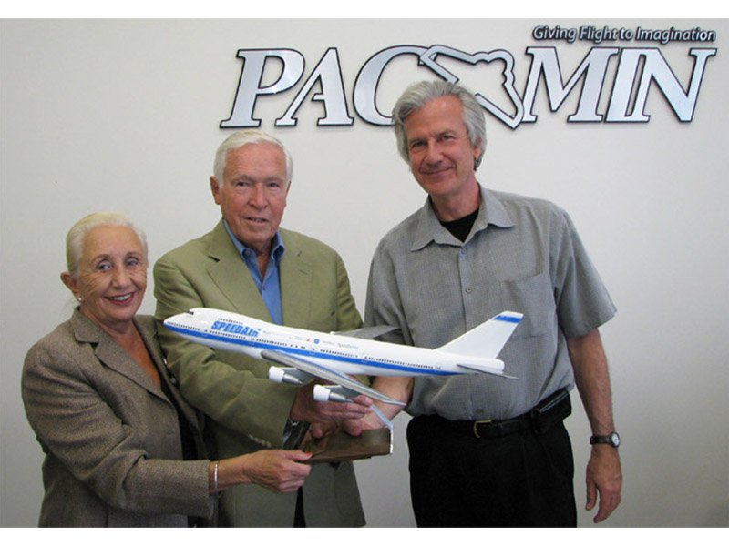 two men and one woman holding SpeedAir plane model