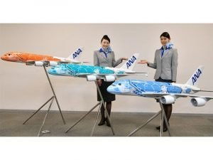 two women standing behind three ANA plane models