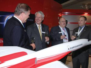 Airbus and Aerion executives celebrate their new partnership with a 1/20 scale Aerion AS2 supersonic business jet model. / Photo courtesy of AIN Online