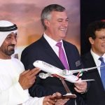 three men holding Emirates plane model