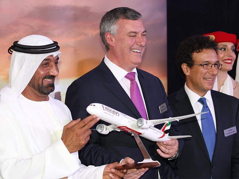 three men holding Emirates plane model