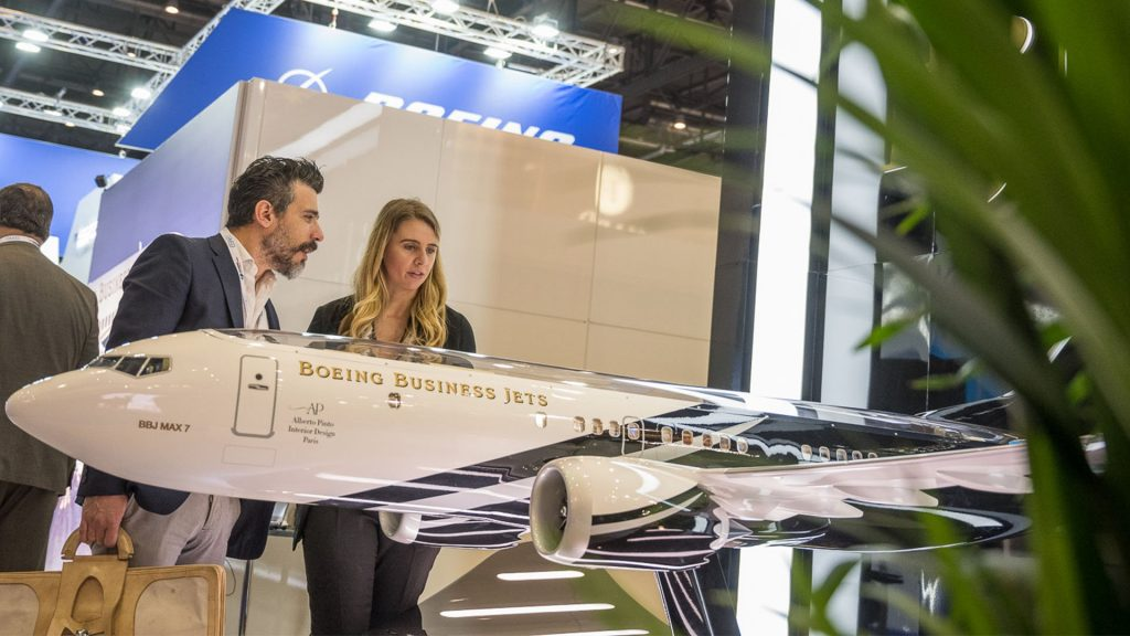 man and woman viewing Boeing exhibit model at EBACE 2109 - product launch solutions