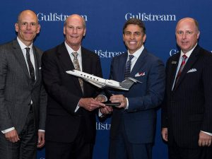 four executives with middle two holding Flexjet model