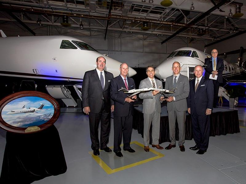 Executives from Flexjet and Gulfstream celebrate the delivery of two G450 with 1/48 scale desktop models of the aircraft. // Photo courtesy of Gulfstream