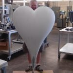 man standing behind large plain white heart