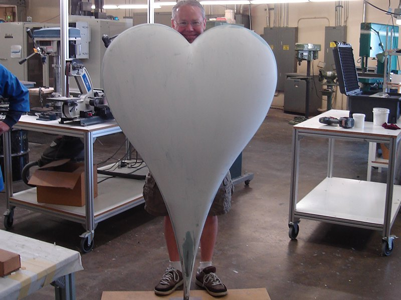 man standing behind large plain white heart
