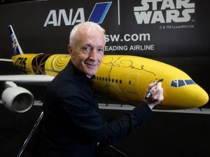 Anthony Daniels autographs a 1/20 scale PacMin exhibit model of the C-3PO ANA Jet at Star Wars Celebration Europe. // Photo courtesy of ANA.