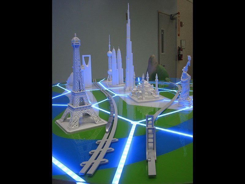 "Key cities are represented by iconic buildings and connected with illuminated ""roads""."